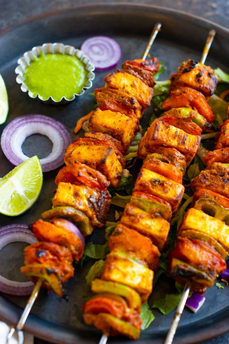 Paneer shashlik kababs served on a round tray with lemon.