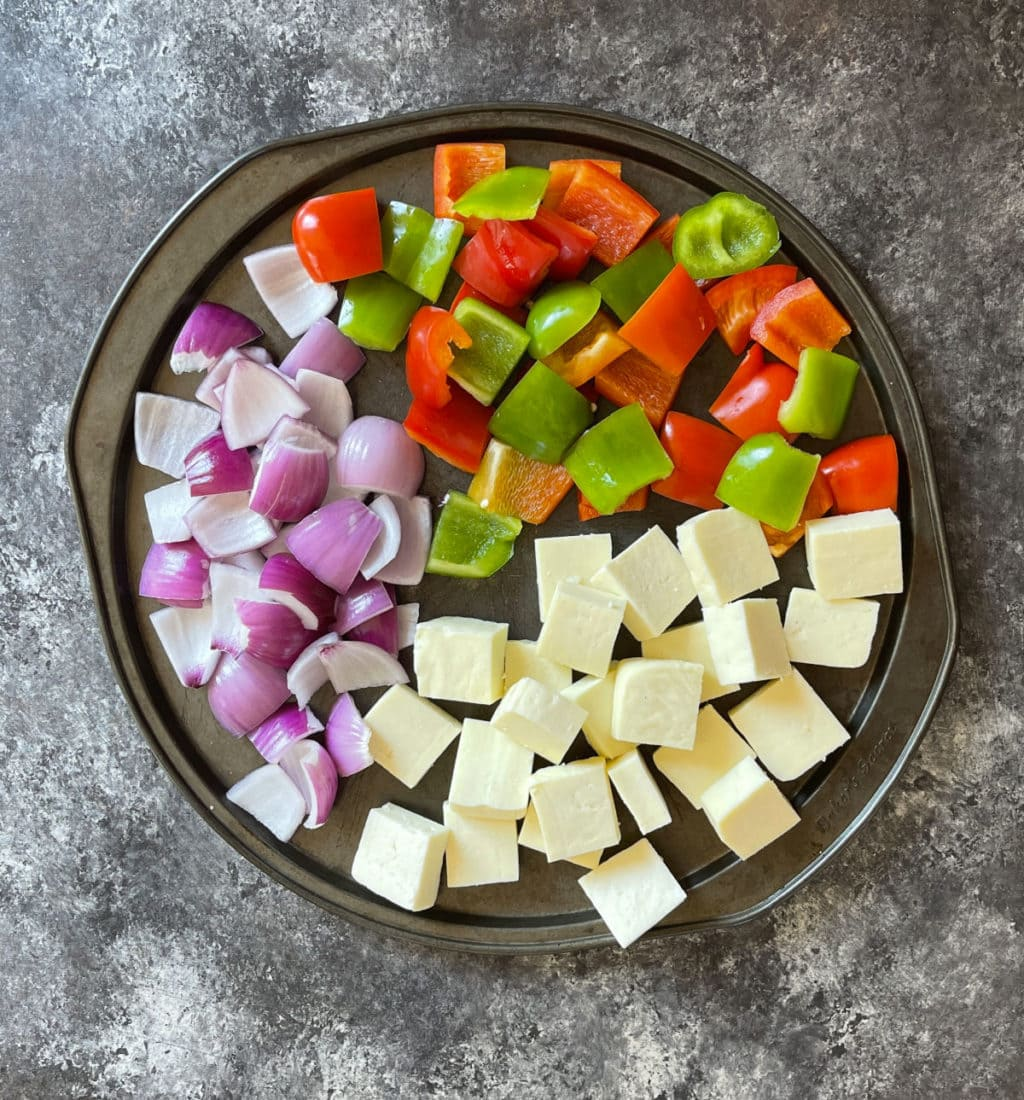 Ingredients to prepare paneer tikka are on the baking tray.
