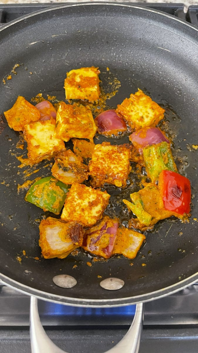 Cooking paneer and peppers on the tawa.