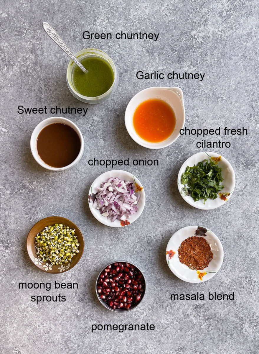 Chutneys, mung sprouts, onions, pomegranate, masalas in different bowls.