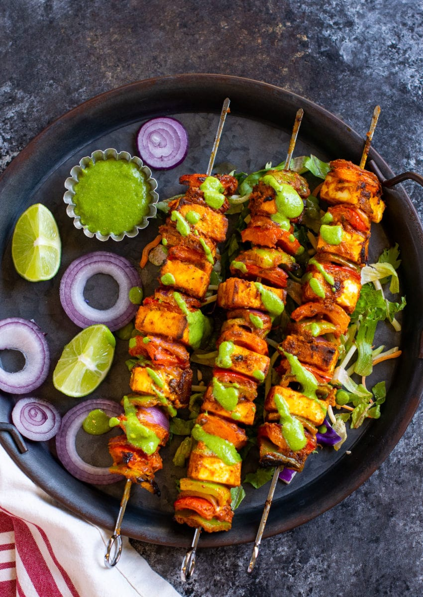 Paneer tikka skewers placed on a black tray with chutney on the side.